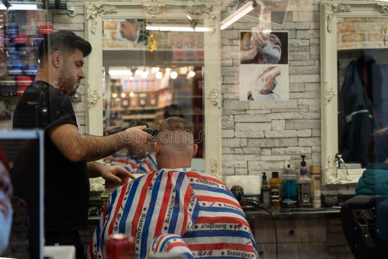 Coiffeur masculin dénommant des cheveux de clients image libre de droits