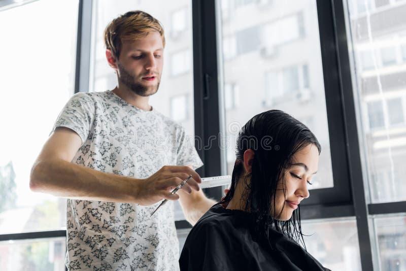 Coiffeur masculin de jeune hanche professionnelle coupant les cheveux foncés de la femme de client au salon image stock