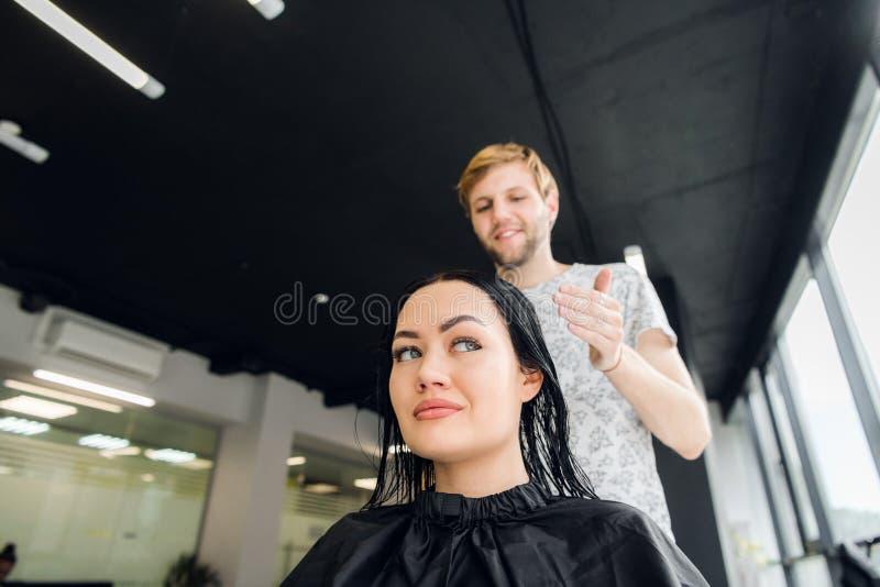 Coiffeur professionnel discutant des préférences femelles de client dans le raseur-coiffeur, choisissant la nouvelle coiffure images libres de droits