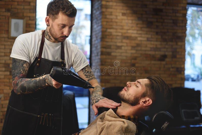 Coiffeur professionnel travaillant avec le hairdryer photographie stock
