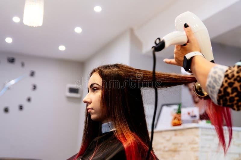 Coiffeur séchant des cheveux de femme avec le hairdryer photos stock