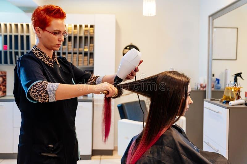 Coiffeur séchant des cheveux de femme avec le hairdryer photographie stock libre de droits