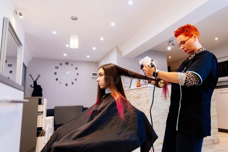 Coiffeur séchant des cheveux de femme avec le hairdryer images stock
