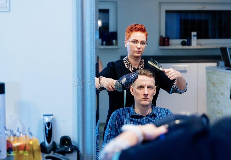 Coiffeur séchant les cheveux masculins de client dans le salon image stock