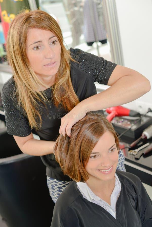 Coiffeur tenant des cheveux du ` s de client dans le style photos stock