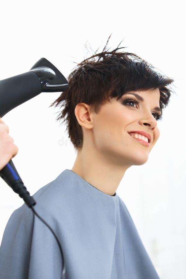 Coiffeur Using Dryer sur les cheveux humides de femme dans le salon.  Cheveux courts. photo libre de droits