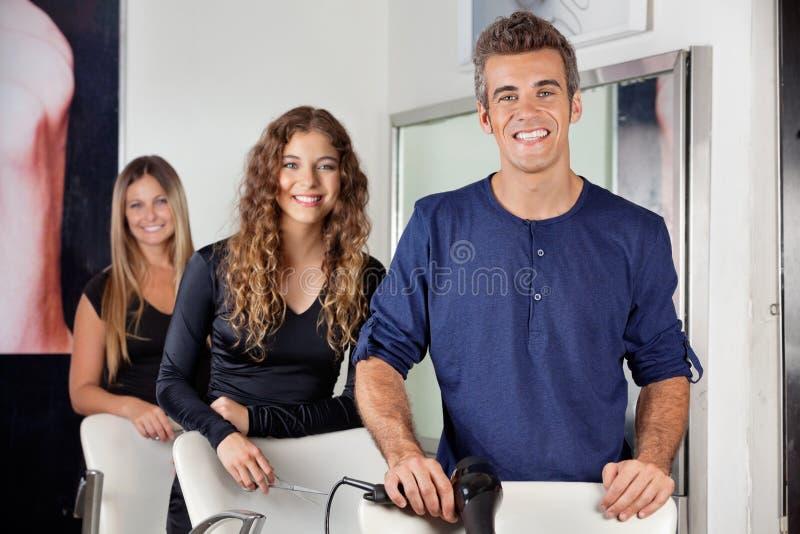 Coiffeurs avec Hairdryer et ciseaux dans le salon image stock