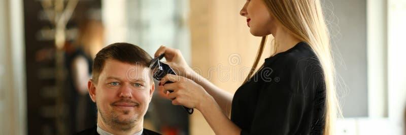 Coiffeuse Making Razor Haircut de femme pour l'homme photographie stock