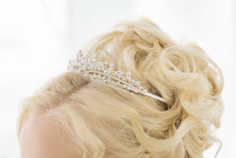 Coiffure avec une couronne de diadème Habillage de cheveux pour la jeune mariée avec un diadème de couronne La couronne précieuse images stock