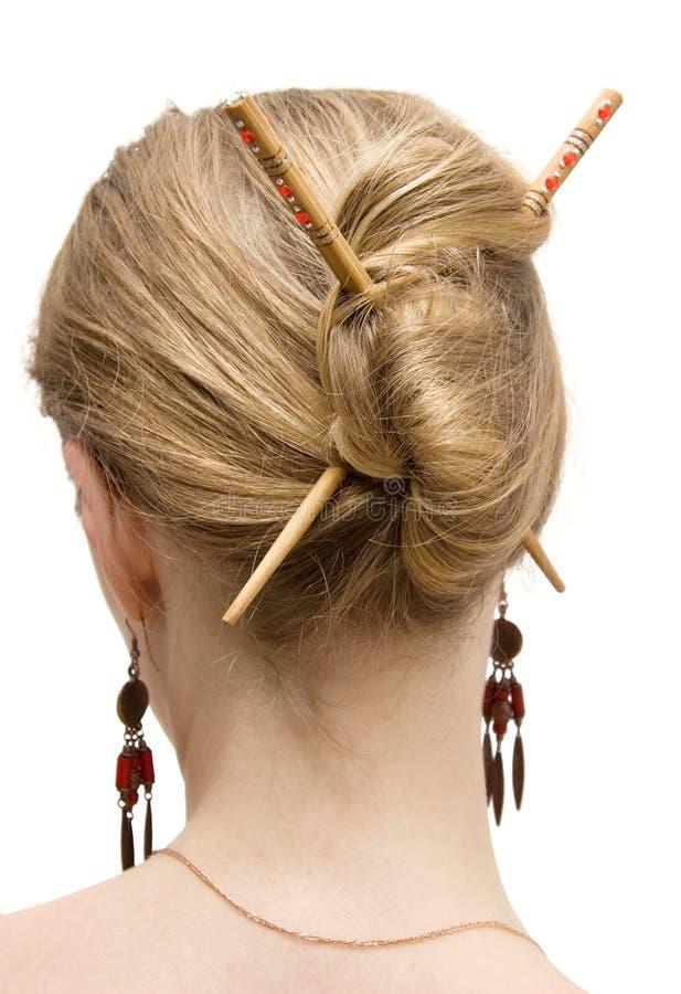 Coiffure de femme avec des bâtons photos stock