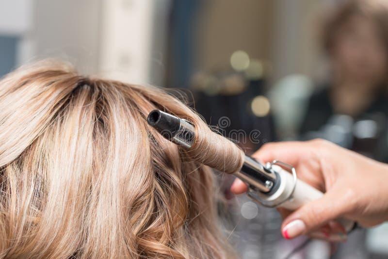 Coiffures femelles sur se courber dans un salon de beauté image libre de droits