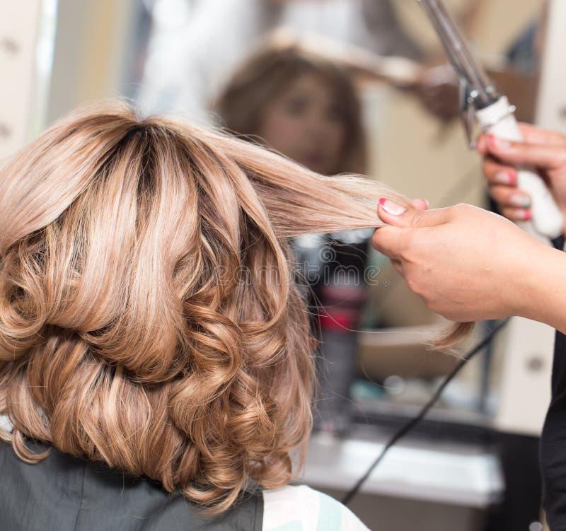 Coiffures femelles sur se courber dans un salon de beauté images libres de droits