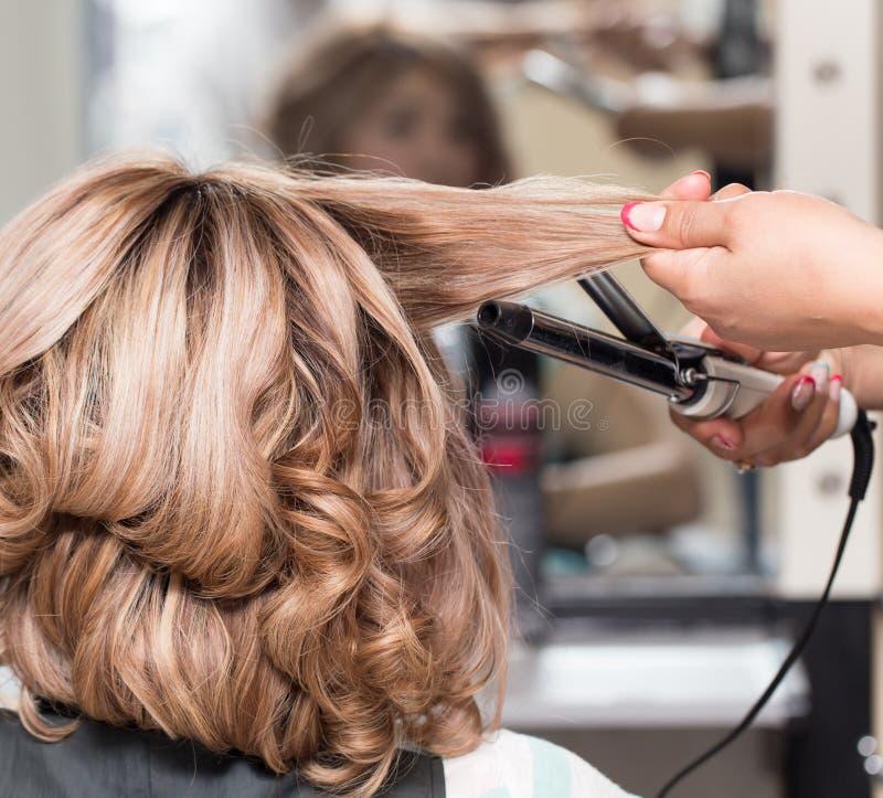 Coiffures femelles sur se courber dans un salon de beauté images stock