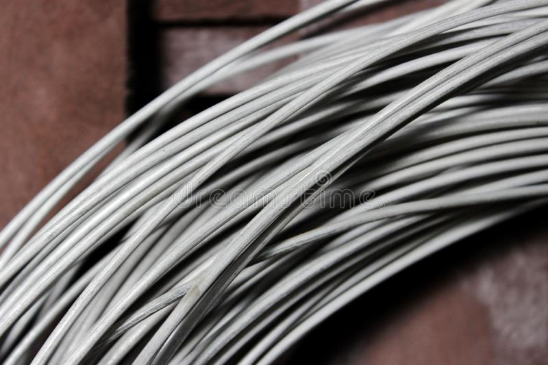 A coil of fechral thick refractory wire hangs in a warehouse of goods for ceramists. Frame of coiled nichrome wire for stock image