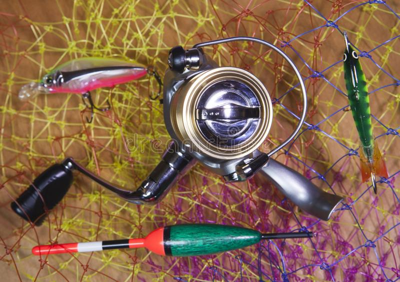The coil, float and baits on a fishing net background.  royalty free stock photography