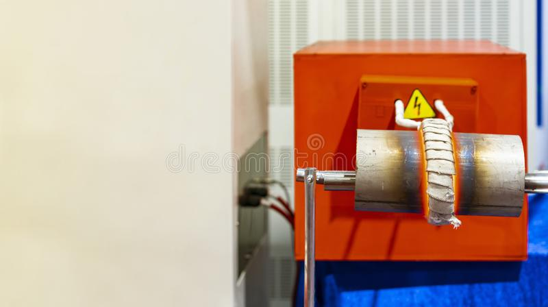Coil and work piece of high volt electric induction heating machine to heat metal pipe or tube in manufacturing industrial work. With copy space stock images