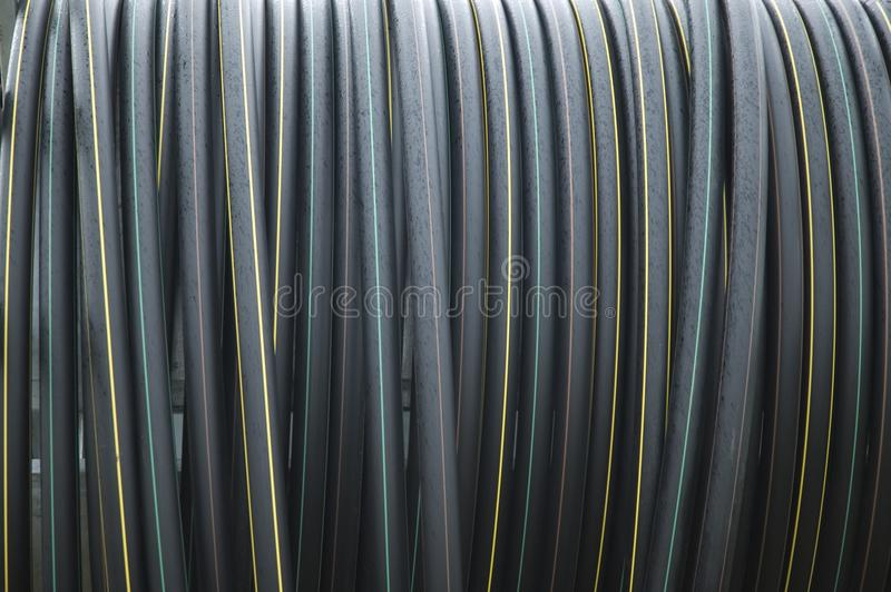 Coiled black hoses with stripes in different colors stock photography