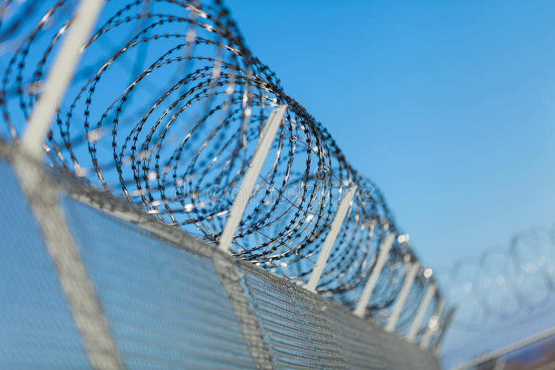 Coiled Razor Wire On Top Of A Fence Stock Image - Image of enclosure ...