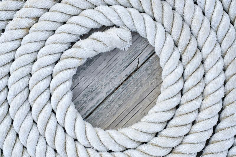 Coiled rope sits on a an old wooddn dock stock photos