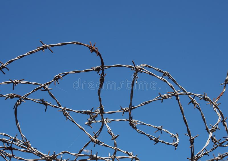 Coiled twisted sharp barbed wire against a bight blue sky royalty free stock photo
