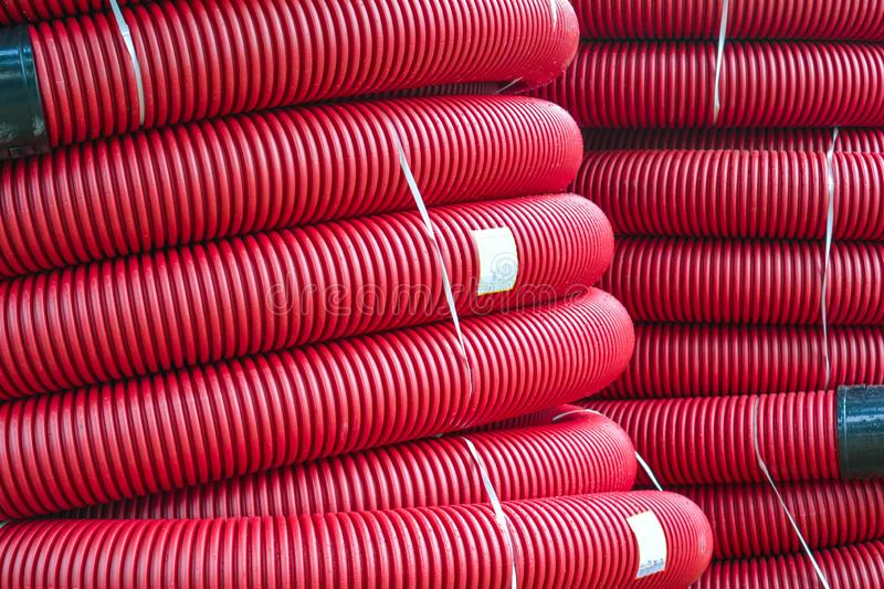 Coils of new red plastic pipe for underground cable protection with rain drops stock images