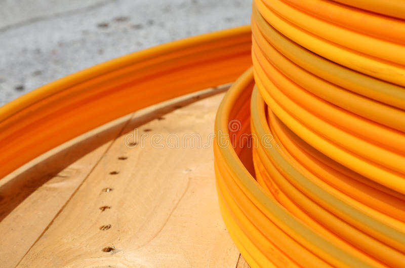 Coils of orange plastic pipes for the installation of undergroun. Long coils of orange plastic pipes for the installation of underground utilities and energy of royalty free stock photo