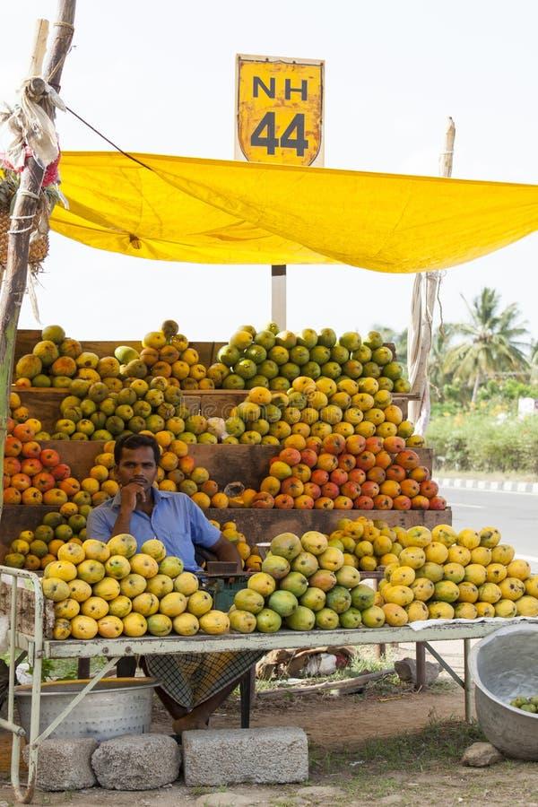 Coimbatore, India - Juni 28, 2015: een verkoper wordt gezien omringd door een verscheidenheid van mango's bij zijn box in Zuideli royalty-vrije stock foto
