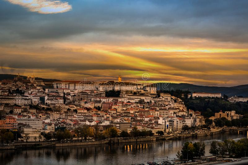 Coimbra city illuminated by the setting sun, Portugal. Panorama of the city of Coimbra along with the river at sunset, Portugal royalty free stock photos