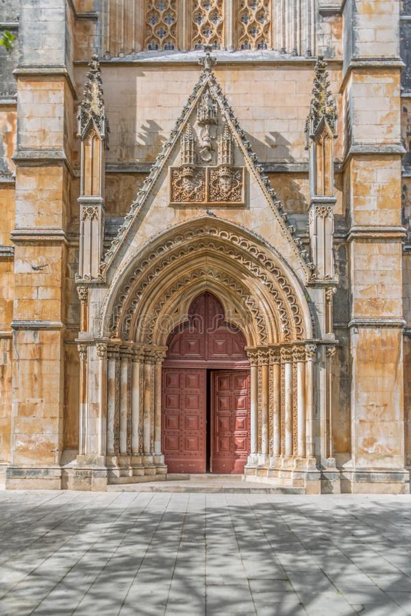 Detail view at the frontal gate and door of the ornate Gothic exterior facade of the Monastery of Batalha, Mosteiro da Batalha, royalty free stock image