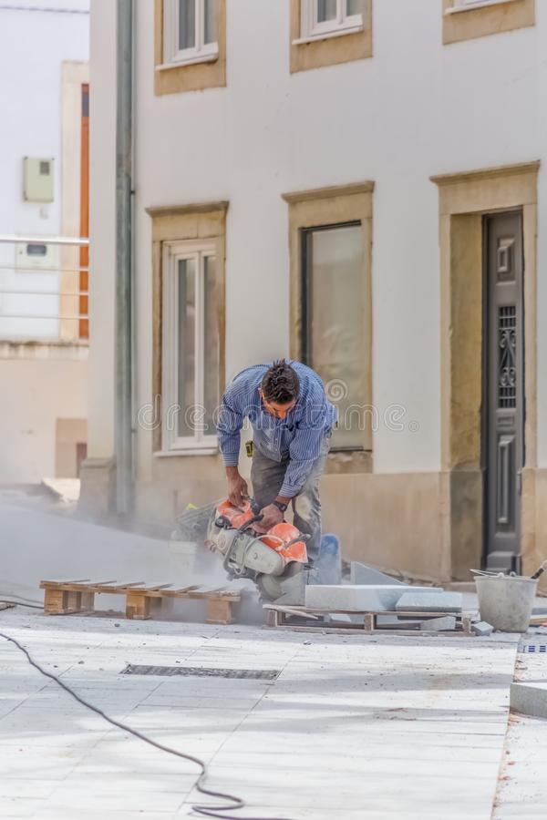 View of construction worker man cutting stone with grinder on street in Coimbra, Portugal royalty free stock photography
