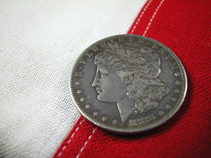Coin-1888 American Silver Dollar. Macro shot of a antique United States One Dollar coin, issued in 1888 resting on the stitching of an American flag stock photos