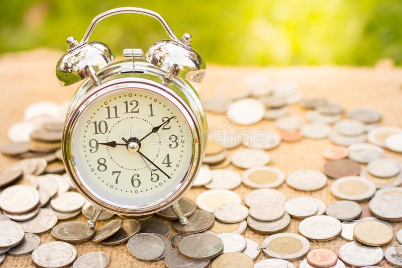Coin and alarm clock are placed on hemp sacks, Money, Financial, Business Growth concept,Saving money for retirement planning. royalty free stock photography