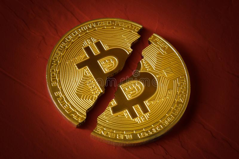 Coin bitcoin is broken in half on red background. The fall and collapse of the course of the crypto currency, the ban on trade stock photography