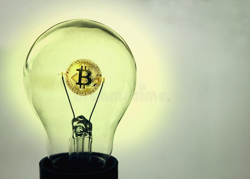 The coin of bitcoin glows inside the old lightbulb royalty free stock photo