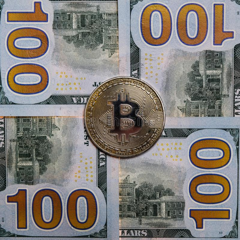 The coin of bitcoin lies on hundred-dollar banknotes. Square frame. Close-up. royalty free stock photos