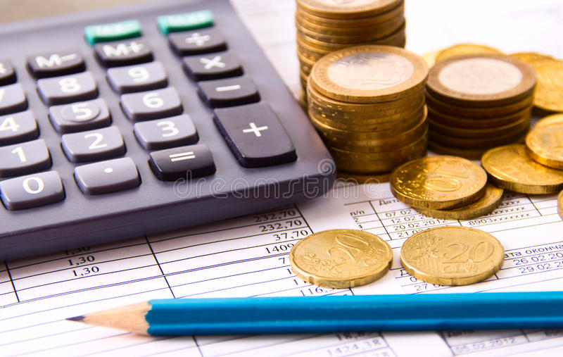 Coin, a calculator, a pencil on the business stock photo