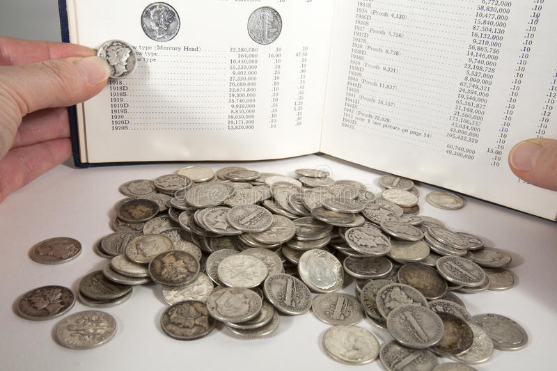 Coin Collecting. Pile of silver dimes with a woman holding a mercury dime against a picture in a coin collecting guide stock photos