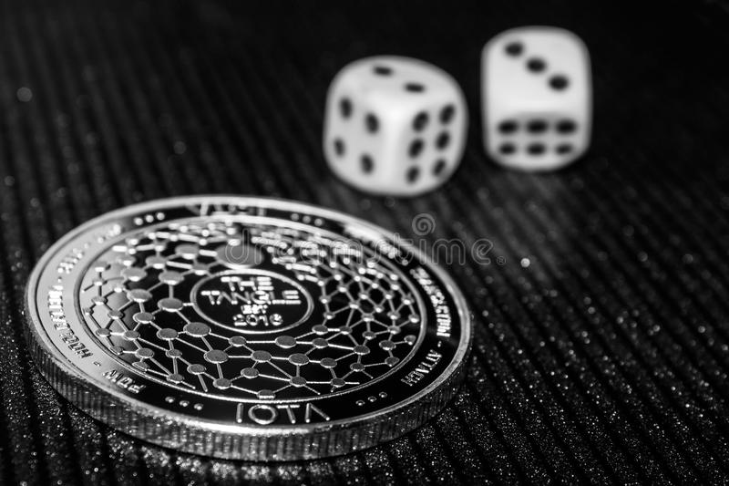 Coin cryptocurrency iota and rolling dice. royalty free stock image