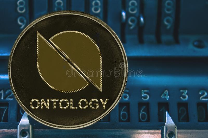 Coin cryptocurrency Ontology ONT against the numbers of the arithmometer. Coin cryptocurrency Ontology and the numbers of the arithmometer. The concept of ONT stock photography