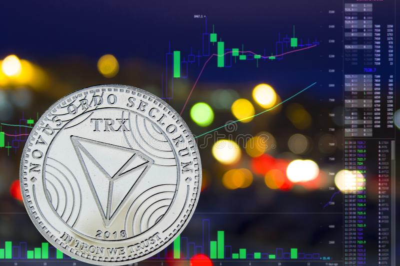 Coin cryptocurrency TRX on night city background and chart. royalty free stock photos