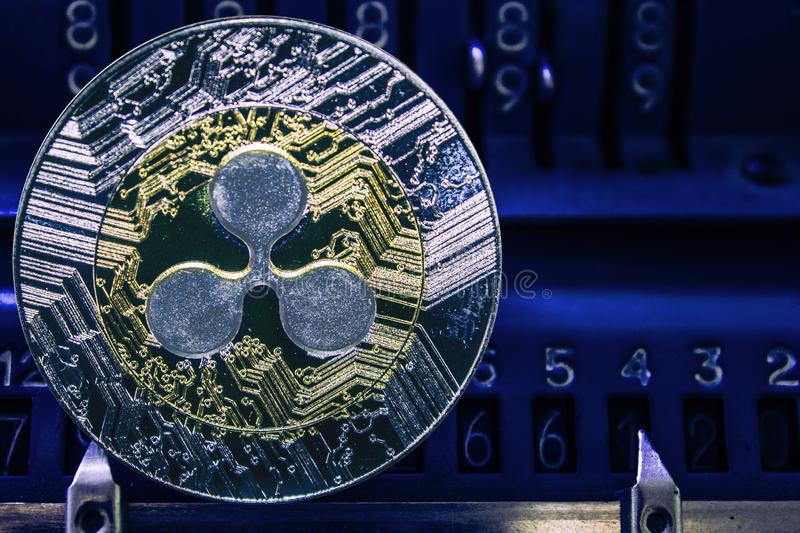Coin cryptocurrency XRP against the numbers of the arithmometer. Coin cryptocurrency Ripple and the numbers of the arithmometer. The concept of production or stock images