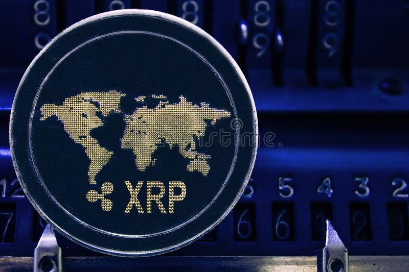 Coin cryptocurrency XRP against the numbers of the arithmometer. Coin cryptocurrency Ripple and the numbers of the arithmometer. The concept of production or stock photography