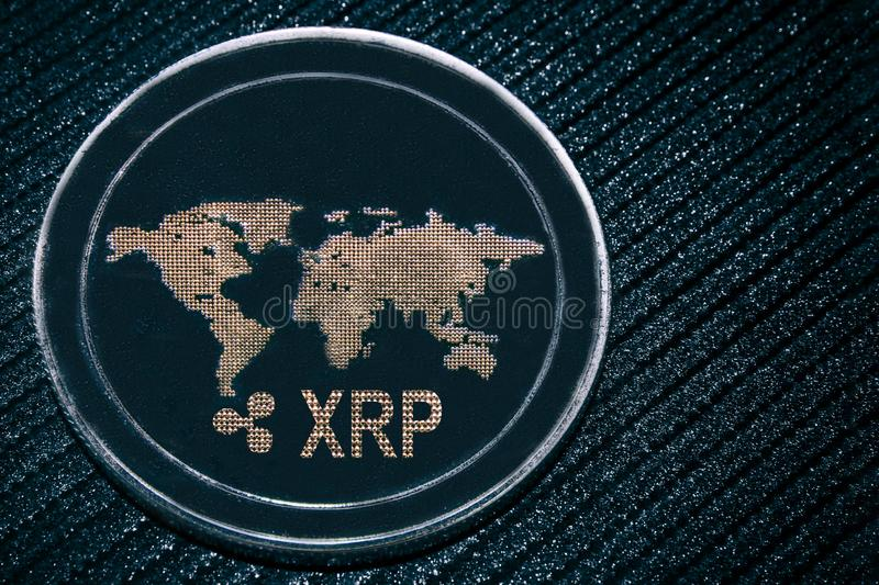 Coin cryptocurrency XRP on a grey background. The ripple. Coin cryptocurrency XRP on a grey shiny background. Ripple stock photo