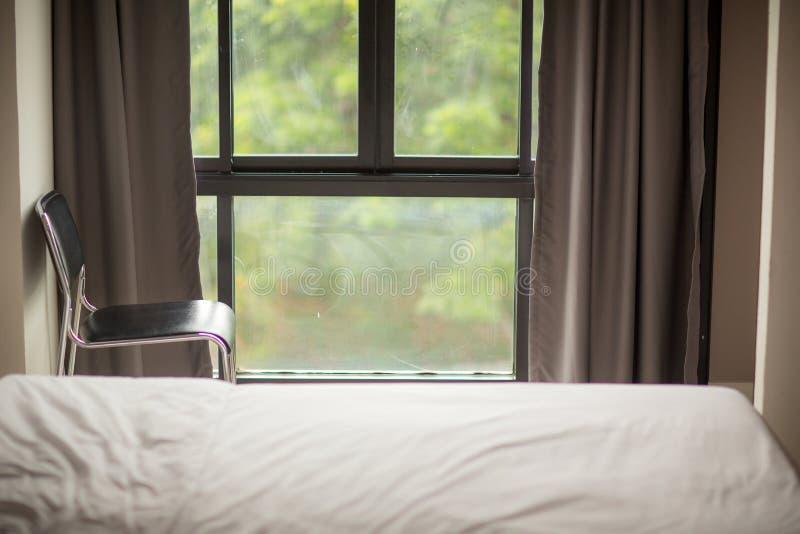 coin de pièce de lit avec la chaise et les fenêtres et les abat-jour image stock