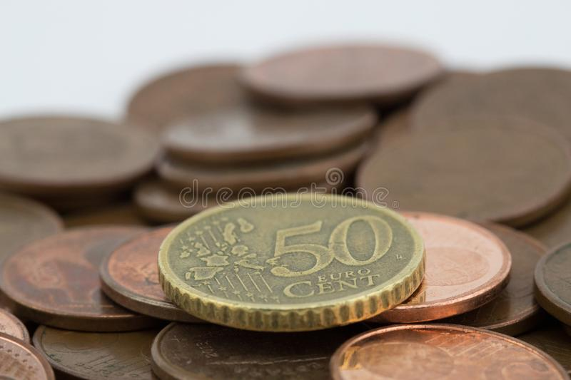Coin of fifty euro cents on several bronze coins of five euro cents. White background.  stock photos