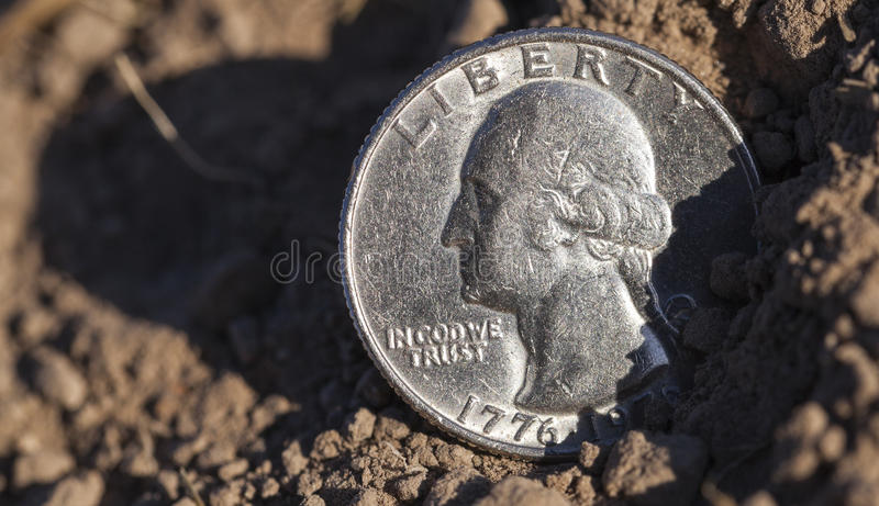Coin on the ground. Photographed close-up of a quarter of the US dollar, lying on the ground, an agricultural field royalty free stock image