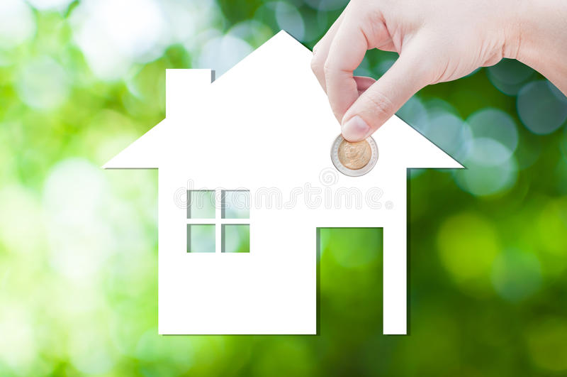 Coin Hand holding house icon in nature as symbol of mortgage,Dream house on nature background. Isolated on white background stock photography