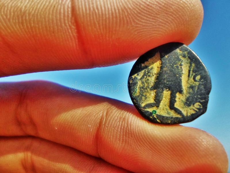 Antique stone coin in between fingers on blue stock photography