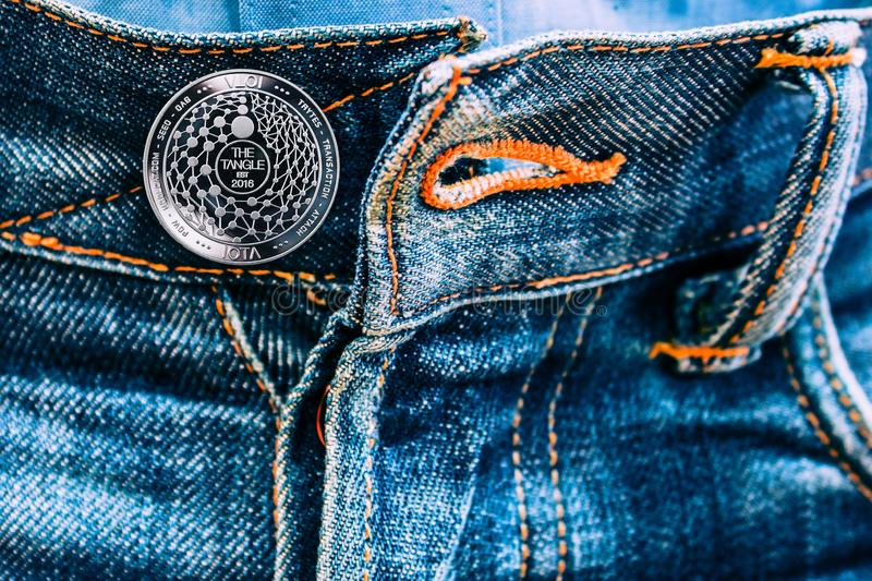 Miota coin instead of buttons on jeans. stock photo