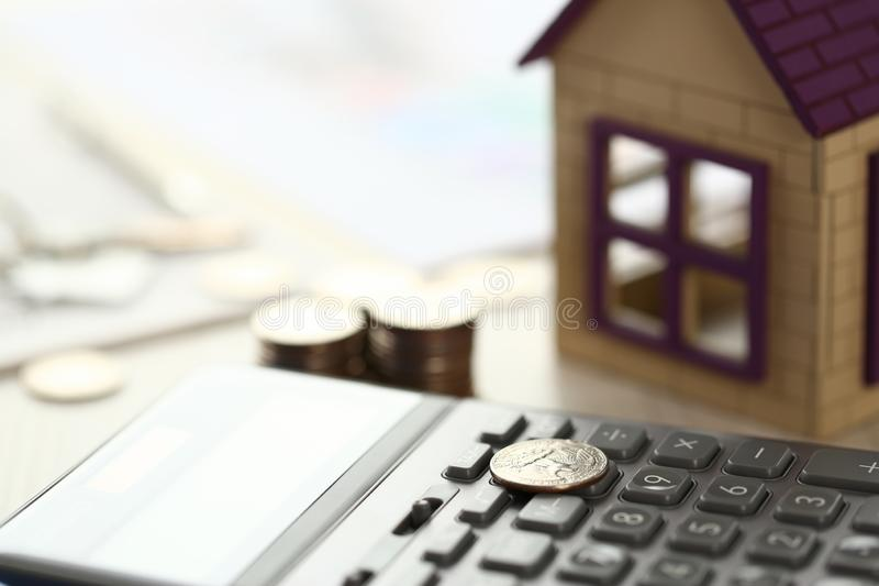 Coin Lay on Calculator, House Model on Office Desk. Sale of Real Estate Items Close Up Shot Partial View. Paper, Bunch of Cash Money Keys Shallow Focus Picture stock photos